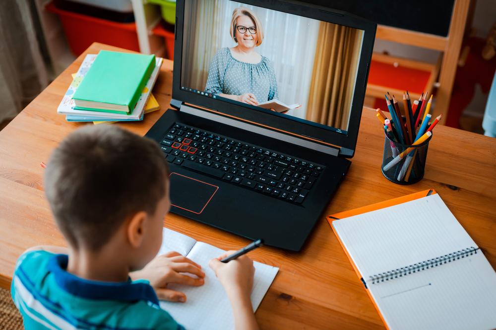 child talks with teacher on laptop