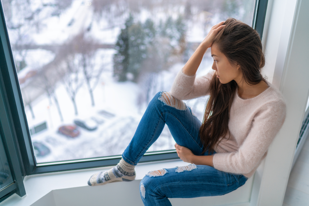 woman with seasonal affective disorder sits alone