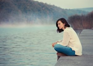 woman with depression sits by lake